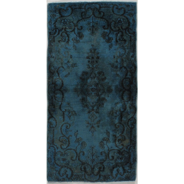 This is a fine example of a vintage over-dyed area rug. These rugs demonstrate a process best described as 'The modern...