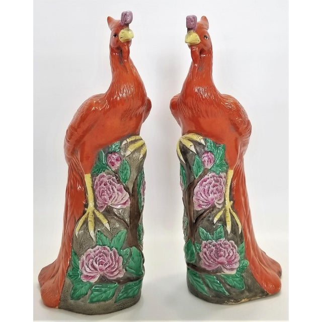 Offering a large pair of Chinese Export ceramic phoenix figurines. These lovely birds are done in the traditional Famille...