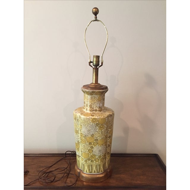 Vintage yellow lamp featuring a petite champagne flower pattern on the body. A gilt wood base adds an elegant touch. The...