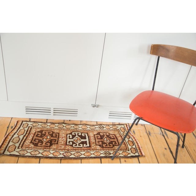 "Triple center medallion rug runner atop a natural brown field. ""HASAM"" is woven in the rug between two of the center..."