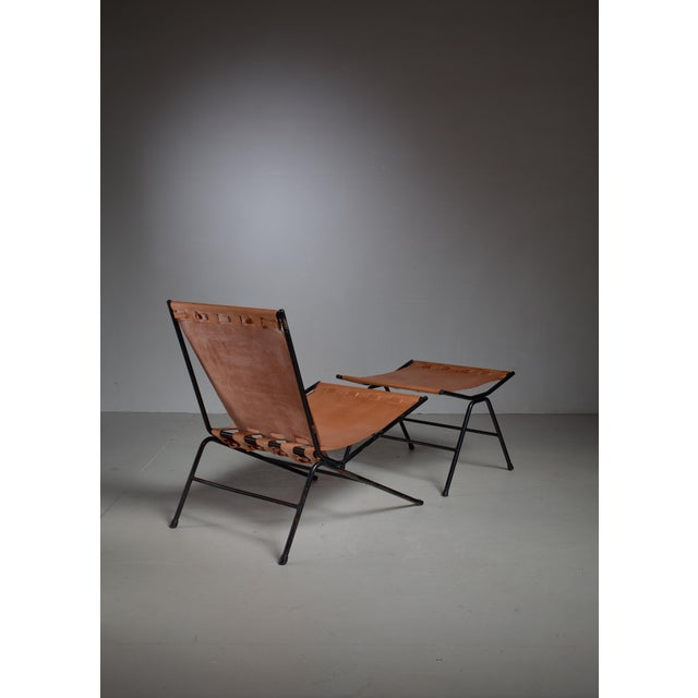 An Allan Gould 'bow'' lounge chair with a matching ottoman. The pieces are made of a black iron frame with a natural...