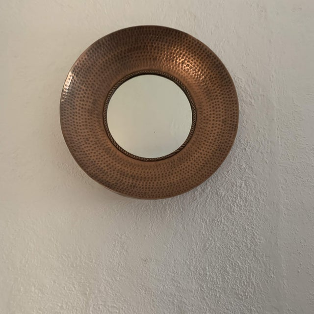 Modern circular wall mirror with deep concave hammered copper frame. Mirror is outlined with twisted copper piping detail....