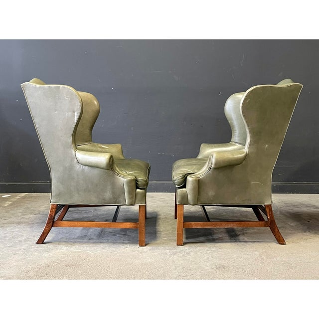 Georgian style leather wing chairs by Ralph Lauren. Covered with a warm buttery olive green leather with the perfect...