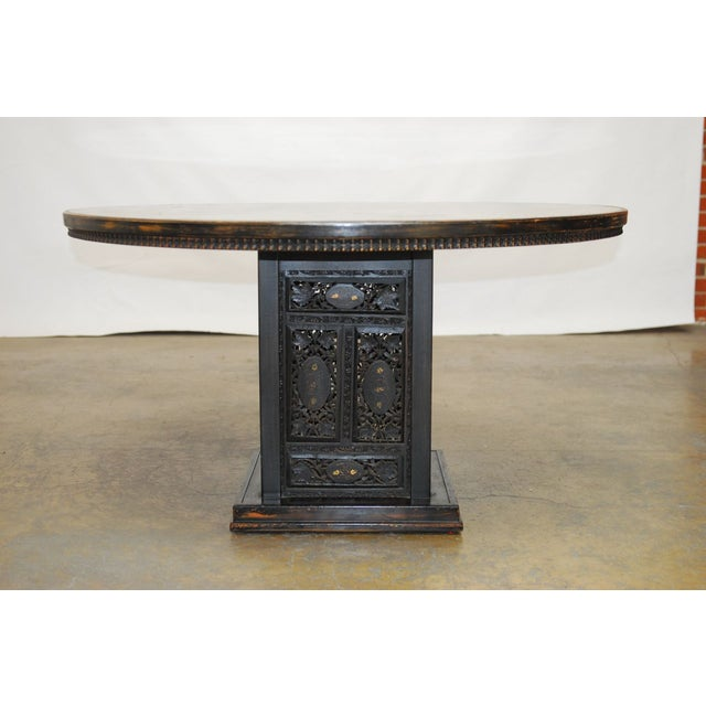 Aesthetic round dining table featuring an anglo-indian carved base with an ebonized finish. This table was produced by...
