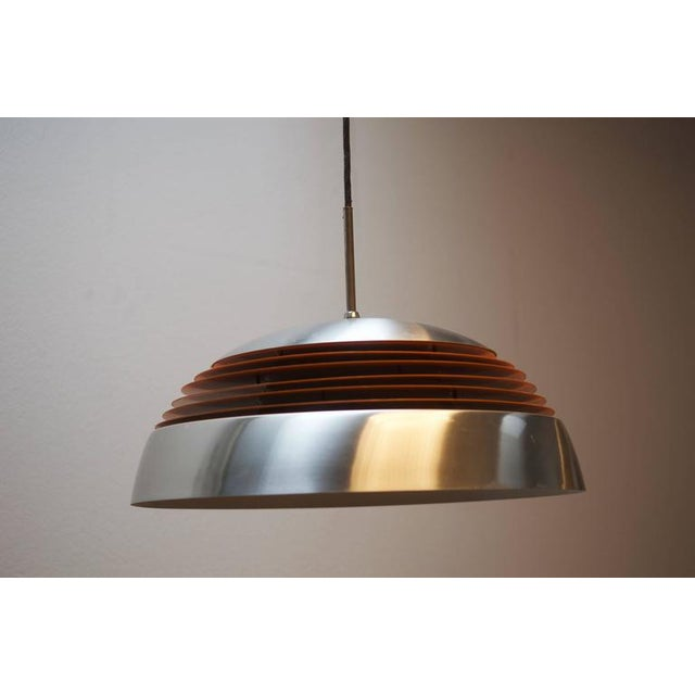 This pendant light features an opaline glass shade with an aluminum frame and an orange painted ring. The piece was made...