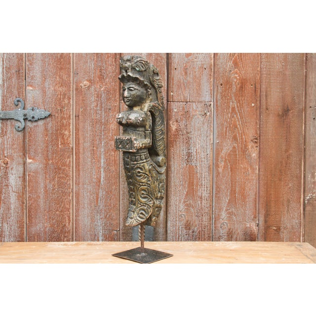 A tribal wood carving of an angel mounted on a custom iron stand with decorative carved features and patterns. Age wear,...