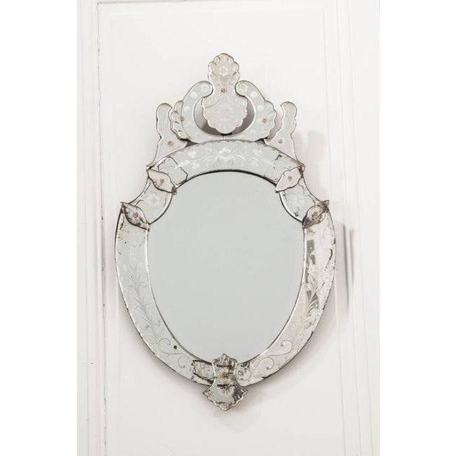 A stunning Venetian wall mirror, with wonderful shield form, from 1880s Italy. The antique uses beautifully shaped mirror...