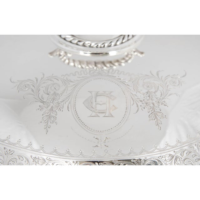 Silver plate serving dish with removable partition. It has a rope trim to the dish with fine engraving around the edge of...