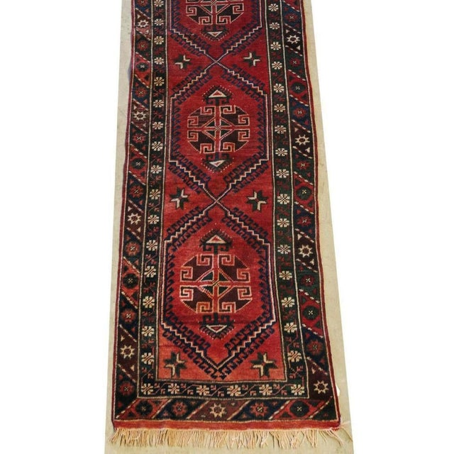Hand-tied wool floor runner. Distressed patina and faded colours of red, blue and black. Overall geometric pattern. The...