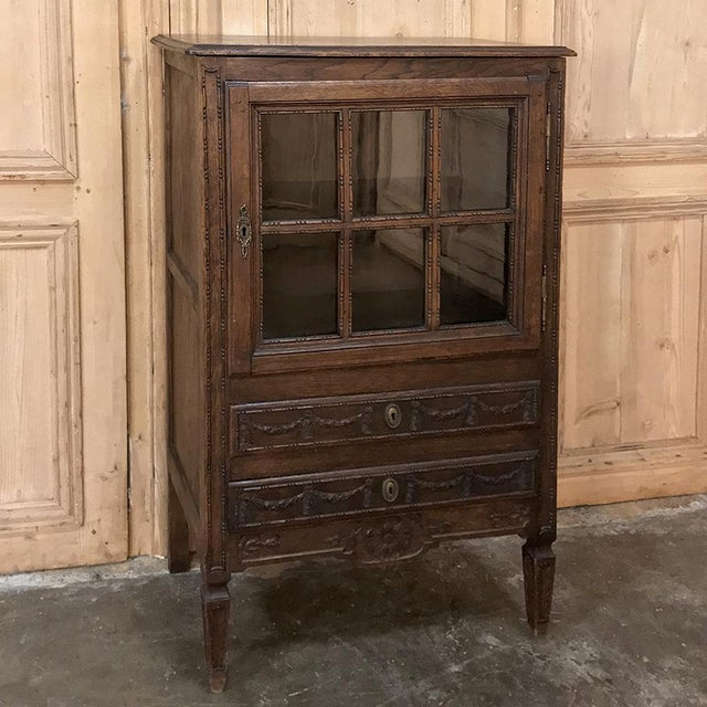 19th Century Country French Louis XVI Vitrine was hand-crafted in the provinces by talented rural artisans in the...