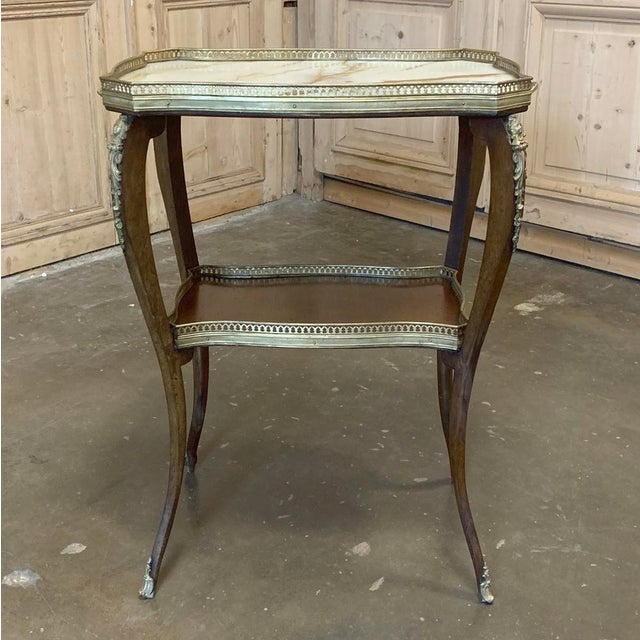19th Century French Louis XVI Marble Top End Table features graceful cabriole legs supporting a lower shelf as well as a...