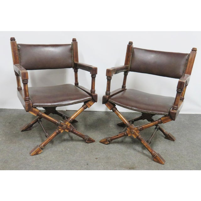 A Pair of Regency directors style chairs, oak frames x base design, with brown leather upholstery, brass nailhead trim.