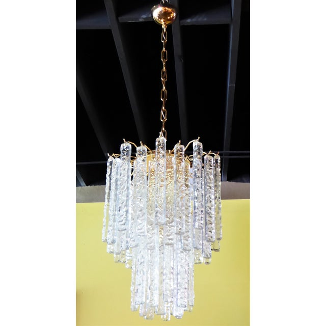 Draped with 54 long textured Murano crystals, this 1960s Mazzega Chandelier beautifully has four inner lights and a...
