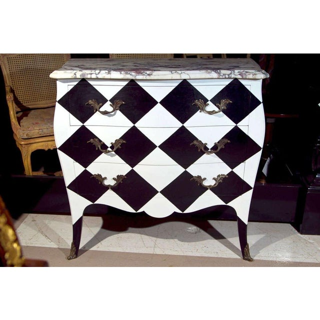 French Louis XV style commode. Features veined serpentine marble atop a checkerboard paint decorated case, fitted with...