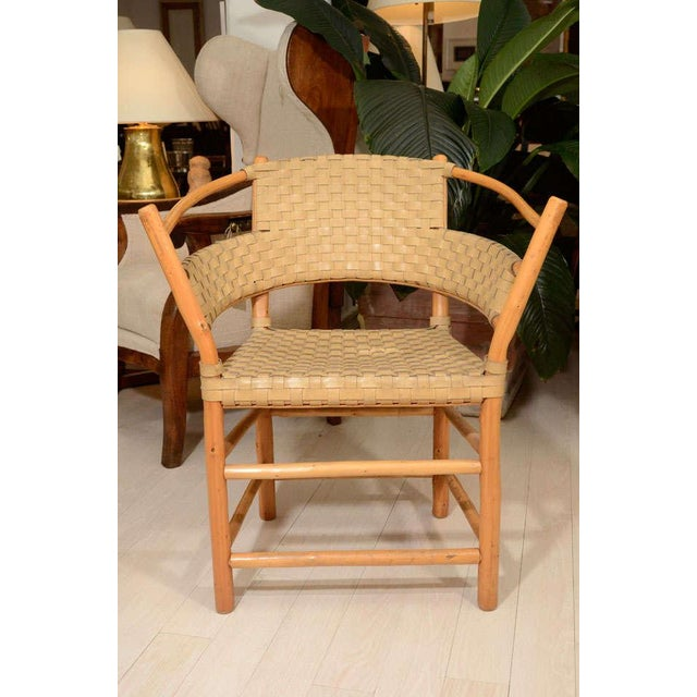 Pair of bamboo chairs with woven ivory leather seats and backs.