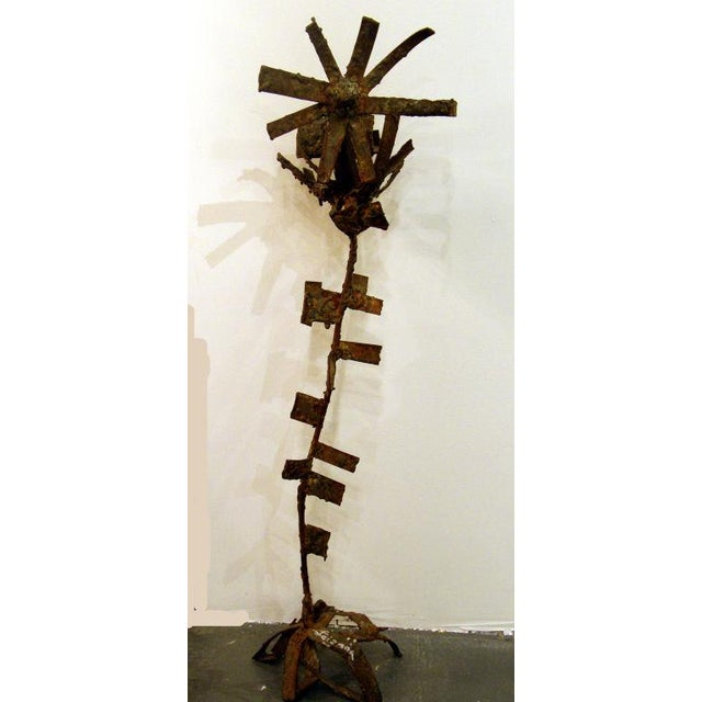 A one of a kind bronze and iron sculpture of a sunflower in a brutalist construction technique with rough cuts, welds, and...