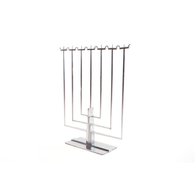 This stately menorah hosts clean, crisp metal modernist lines that echo former design periods including Deco and Bauhaus.