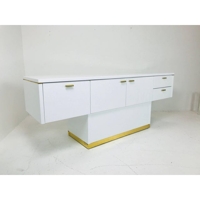 Lacquered T-Console/sideboard with brass accents. Storage includes three door with open storage and two drawers....
