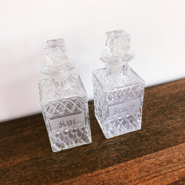 """Set of 2 vintage crystal Scotch and Rye decanters. The front of each decanter features """"Scotch"""" and """"Rye"""" inscriptions...."""