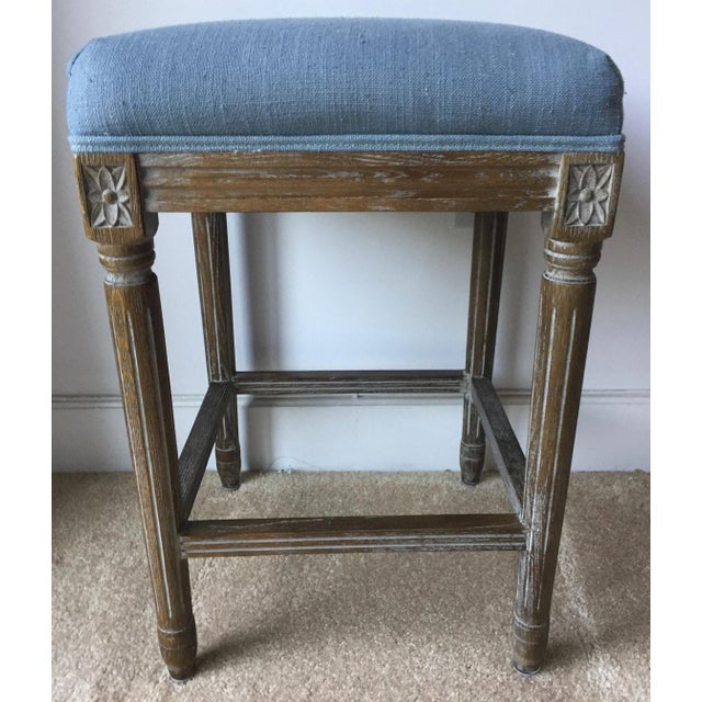 This absolutely charming pair of French style carved pickled wood square stools feature blue linen self-welted upholstered...