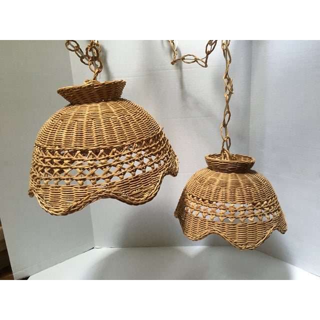 "Very rare pair of vintage natural wicker swag pendant lights. Larger shade measures 14.5""diam. x 10.5""h; smaller shade..."