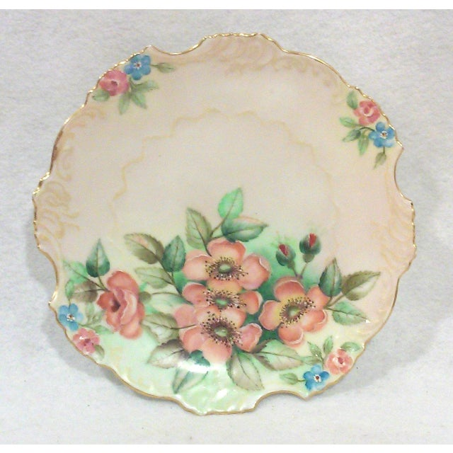A hand painted porcelain cabinet plate with an expertly executed floral design and a 24K gold rim. This German porcelain...