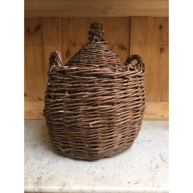 Fantastic antique rustic demijohn wine jug from the 1800s. The basket is made of dark hand woven branches and twigs that...