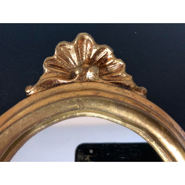 Vintage florentine gilt mirror. Shell designs at top and bottom. Red felt back.
