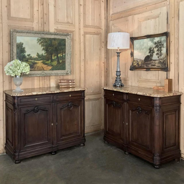 PAIR of 19th Century French Walnut Louis XV Marble Top Buffets is a study in understated elegance, with subtly carved...