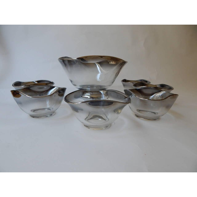 """A Mid-Century Modern 1960s set that includes seven pieces. It includes: one large bowl 10""""W x 6.5""""H and six small bowls..."""