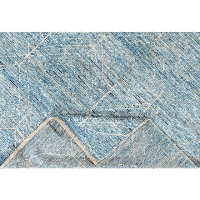 A 21st century Moroccan-style rug, hand knotted from the highest quality wool with a light blue field and allover abstract...