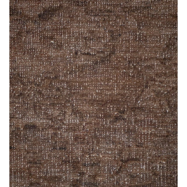 This revival Agra style rug features a burgundy-brown field with an overall design of palmettes and floral vine around...