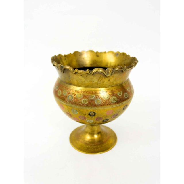 A beautiful brass vase with multi color floral etchings. Made in the mid 20th century.