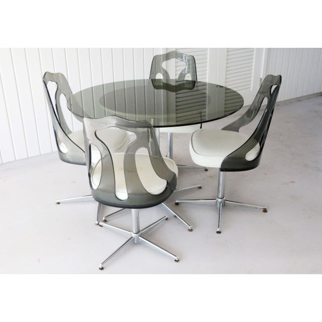 A 1970's dining set with four chrome and smoked lucite chairs, a chrome table base, and smoked glass top. The thick...