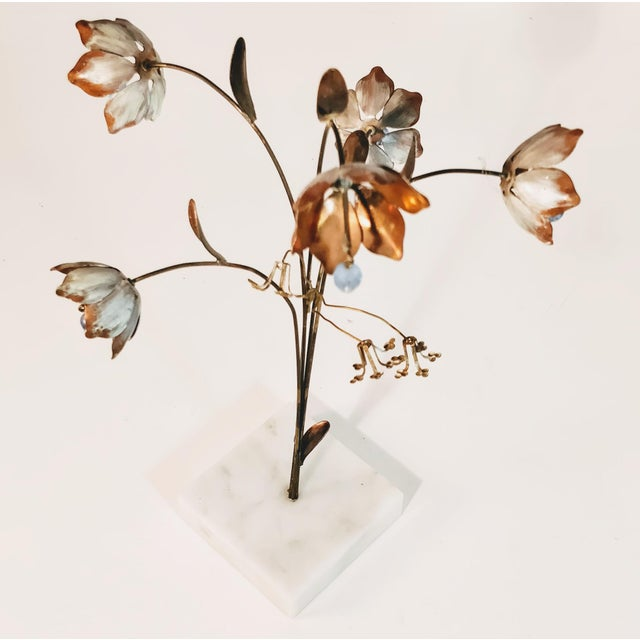Tabletop size, this is a vintage brutalist metal sculpture of flowers atop a leafy stems. The larger flowers are copper...