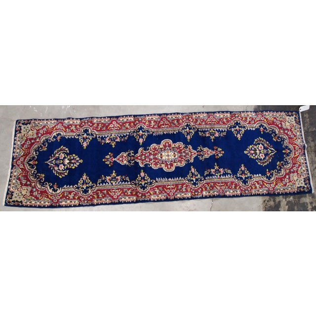 Handmade antique Persian Kerman runner in bright blue and red wool. The runner is from the middle of 20th century in...