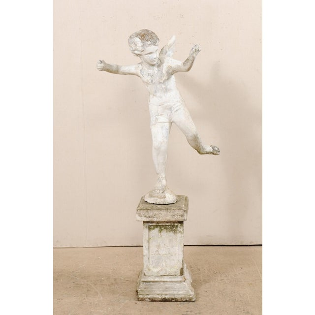 A tall French garden sculpture of a winged boy angel from the early 20th century. This antique statue from France sweetly...