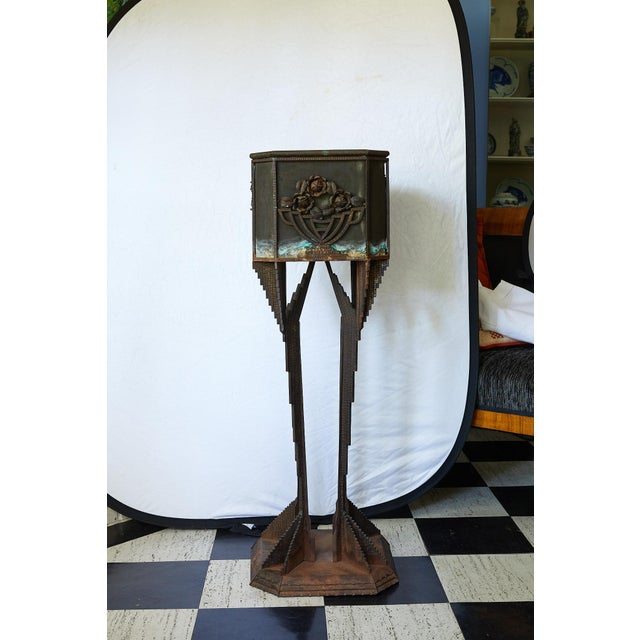 Fabulous Art Deco sculptural iron pedestal supporting a square wire mesh planter with decorative appliqués of metal...