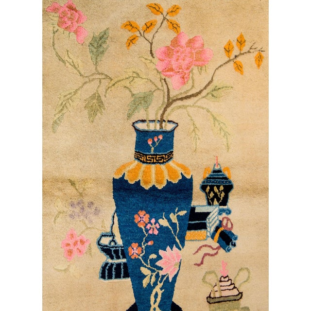 An unusual early 20th Century Chinese Art Deco rug with a large vase decorated with peony blossoms and filled with...