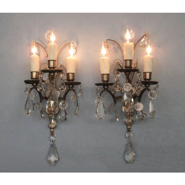 A pair of Italian Baroque silver patinated bronze and crystal sconces, circa 1860, each with three candle arms. The...
