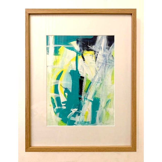 This original abstract acrylic painting is filled with hues of blue, green and yellow. Framed and matted in light wood...