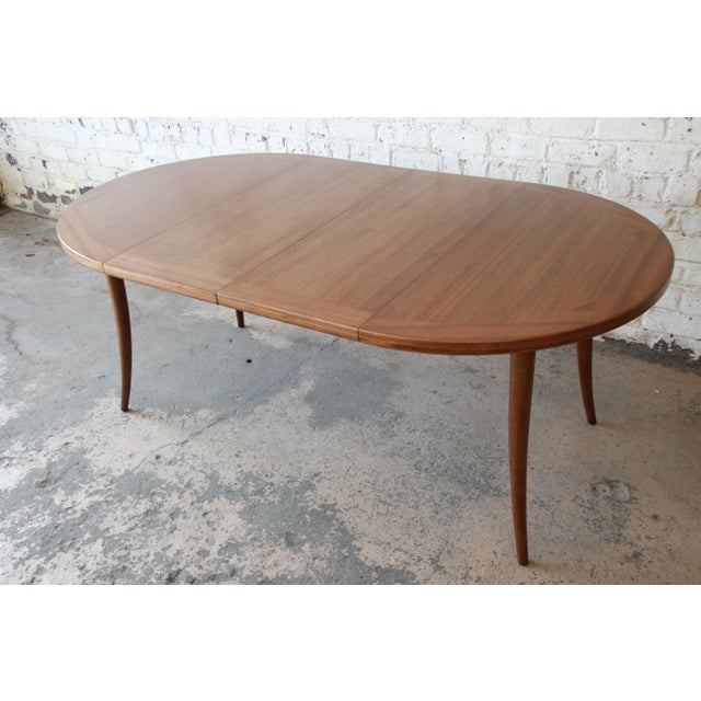 Offering an outstanding mid-century modern saber leg extension dining table designed by Harvey Probber. The table features...