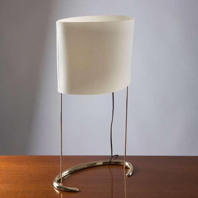 """""""Gala"""" table lamp by Paolo Rizzatto for Arteluce. Brass curved base and lampshade in synthetic fiber."""