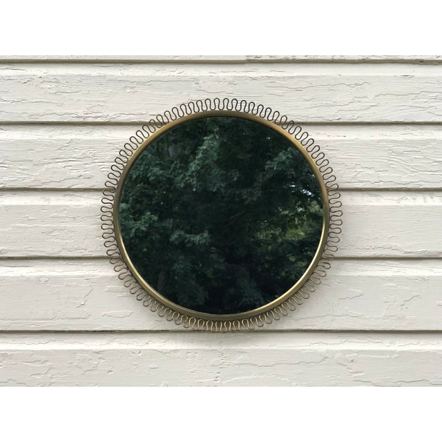 Round brass mirror in the style of Gio Ponti. Original mirror glass on a solid wood base with brass ring and wire work....