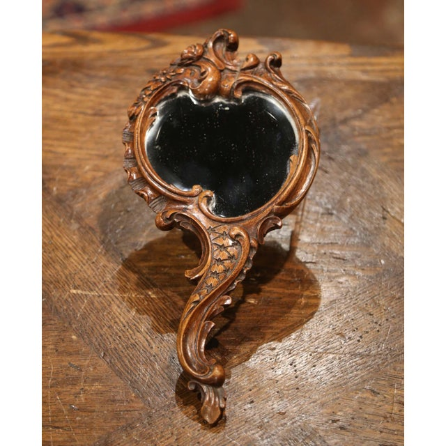 Crafted in France circa 1870, the antique Louis XV style hand mirror with elegant serpentine handle, features hand carved...