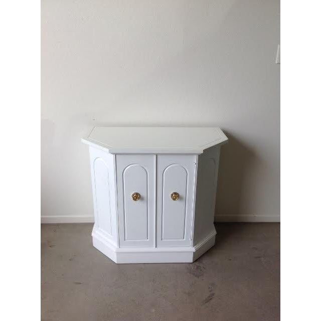 Glam up your home with this angular Hollywood Regency style cabinet. The cabinet features a white semi-gloss finish and...