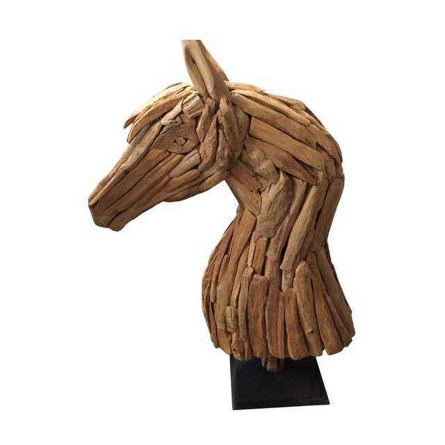 Tall horse sculpture made from pieces of carved and rough-hewn salvaged wood. Wood pieces assembled with metal nails....