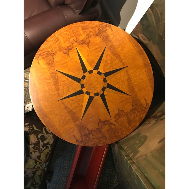 A round occasional table in Olive burl centered by a marquetry pattern of an eight-pointed star in alternating ebony and...
