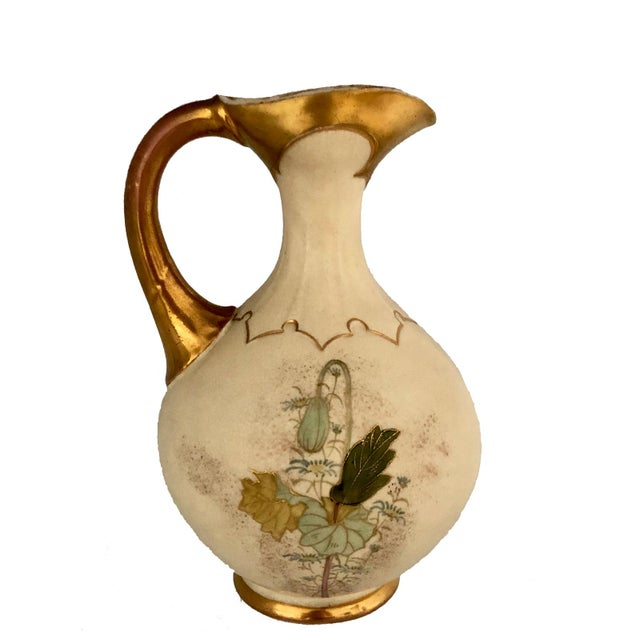 A late 19th or early 20th century painted Austrian pitcher. The handle and base are gilded and all sides with colorful...