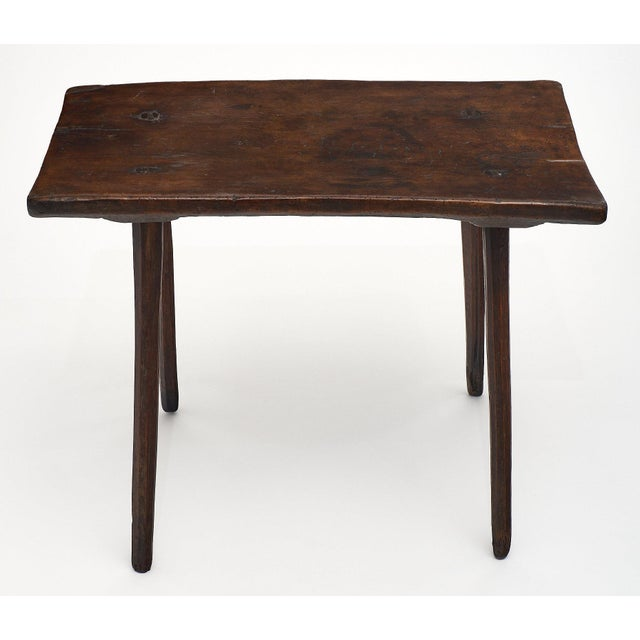 A single walnut plank Italian farm wood side table with four round, hand-carved legs pegged into the top. This primitive...